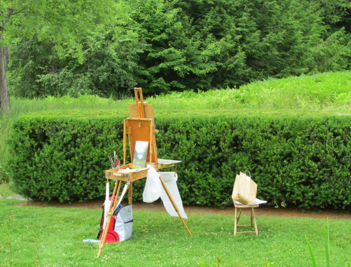 painting on easel by hedge