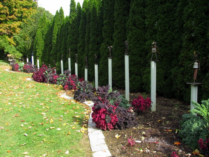 arborvitae hedge, kale, coleus, statues