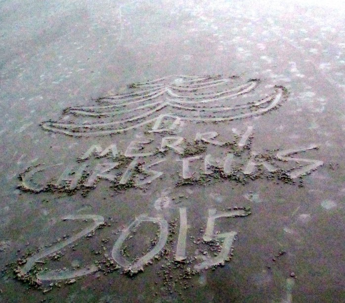 Someone had sketched a tree and Merry Christmas 2015 on the sand, mid-beach
